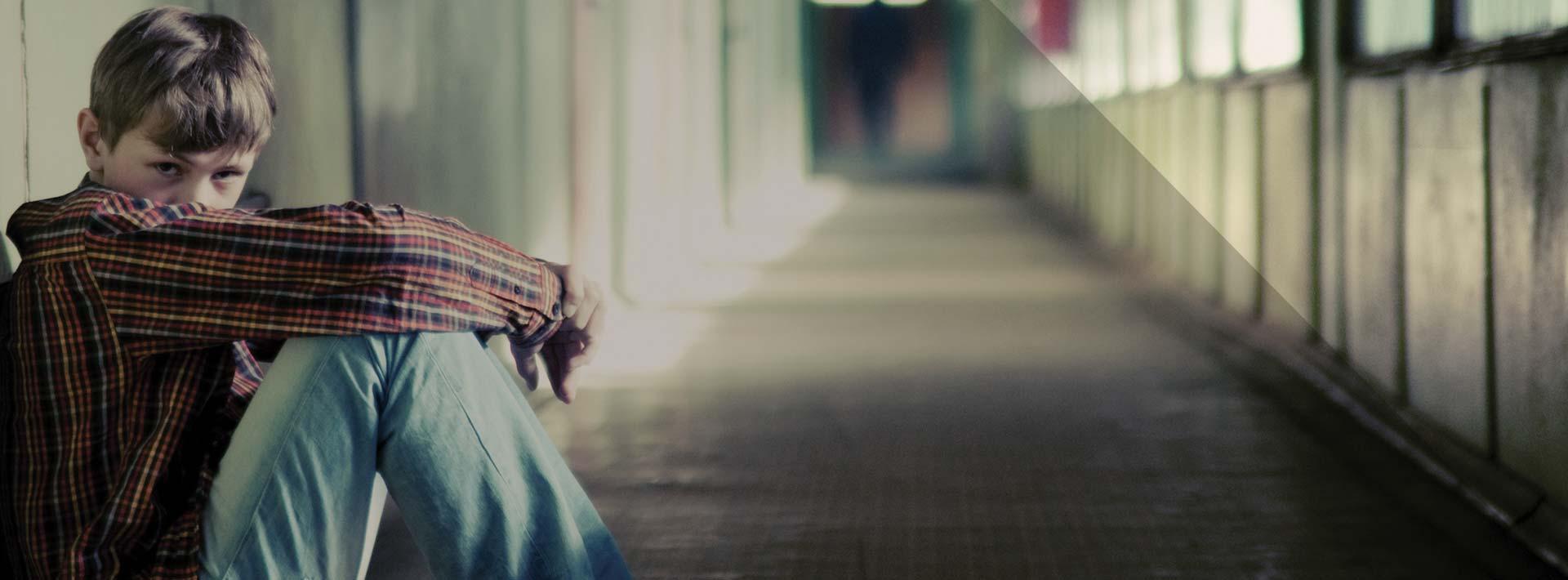 Child sitting alone in an empty corridor