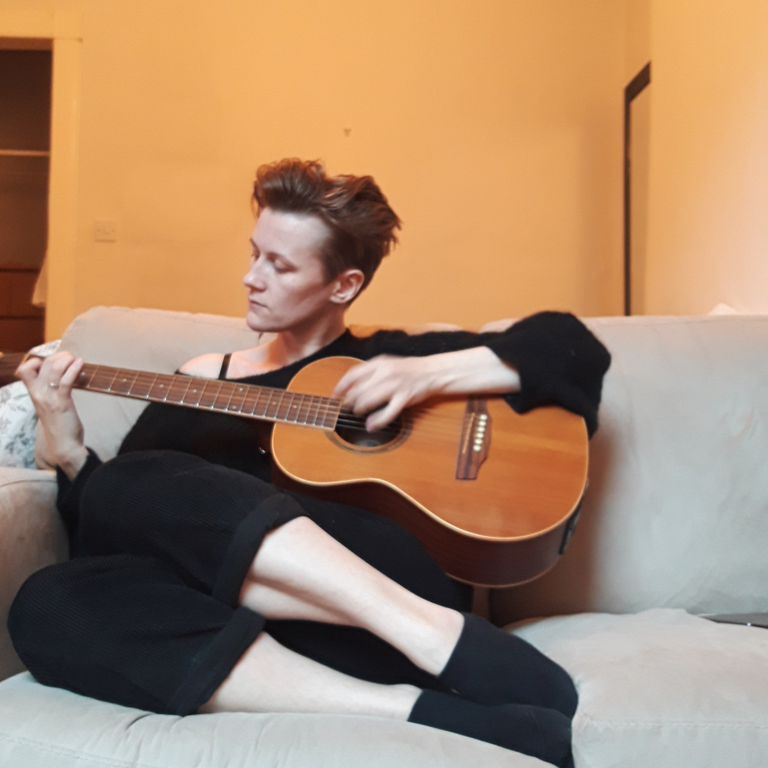 A picture of Emma, curled on a seat and playing an acoustic guitar.