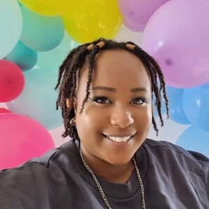 A Black woman smiles at the camera. She has short hair, wears a grey jumper and a necklace. Behind her are multicoloured balloons.