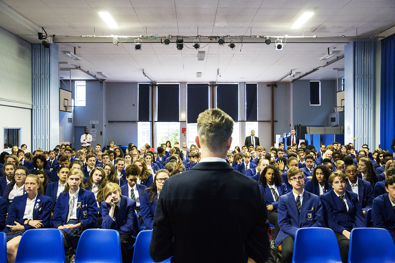 Teacher standing in front of school assembly