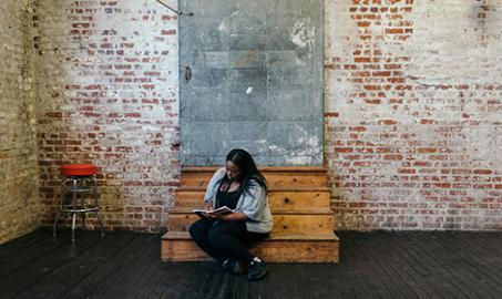 Person of colour seated on steps, writing in a notepad