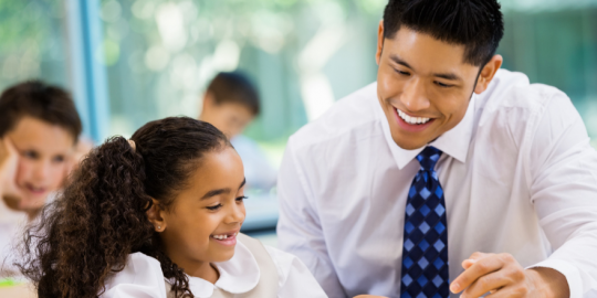 An adult of colour in shirt and tie talks to a child of colour with black hair