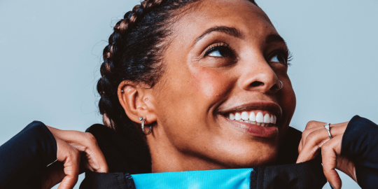 A Black woman with braided hair, and an earring and nosering, wears a black cagoul with a fluorescent-blue neck and looks up and to the viewer's right while smiling