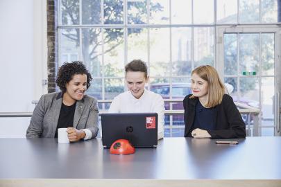 Three individuals sat around a laptop