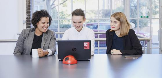 Three colleagues around a laptop