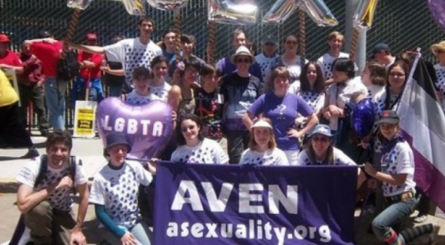 Group of people celebrating on a street with a balloon that says LGBTA and a sign that says AVEN asexuality.org