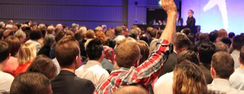 Audience member with hand raised at Workplace Conference
