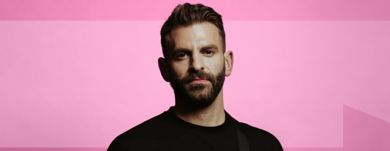 White person stands in front of a pink background, wearing black, with a beard and short hair. An arrow is visible in the background