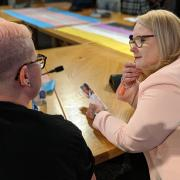 An MSP talks with a trans person at an event held at the Scottish Parliament