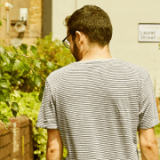 A white man walks down a sunny street, back to the camera, head looking down at the pavement