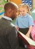 Black teacher reads a book to a white schoolchild in a classroom